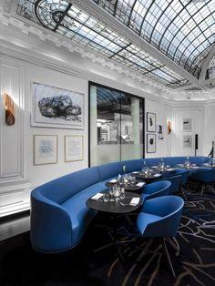 restaurante com sofá e poltronas curvas e teto de vitral