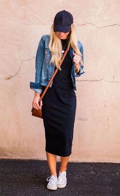 Street style look com vestido midi, jaqueta jeans, tênis branco e boné.