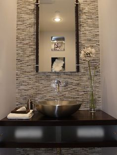 Powder room featuring Erin Adams glass mosaic tile on wall (from Ann Sacks). Kohler stainless steel vessel sink & wall mounted faucet. Espresso stained Alder wood custom floating counter with sliding frosted glass panels to conceal storage