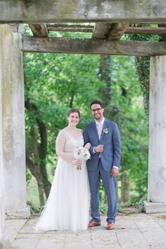 Bride in blush dress with pastel bouquet and groom in navy suit with blush tie by the Bandstand at Historic Shady Lane