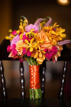 A pink and orange bouquet with roses and orchids | Brides.com