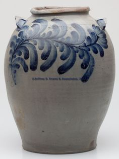 "STAMPED ""H.C. SMITH / ALEX A / D C"", ALEXANDRIA, VIRGINIA DECORATED STONEWARE JAR, salt glazed, approximately 4 gallon capacity, bold ovoid form with single incised ring, rounded rim, and arched tab handles, straight cut-off lines under base. Exuberant brushed cobalt decoration comprising a horizontal floral vine on front, three seven-petal vertical leaves on reverse, and a single five-petal leaf below each handle, additional cobalt at handle terminals. Strong full mark. Hugh Charles Smith's…"