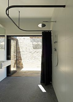 indoor-outdoor bathroom, black penny tile, vintage feel. via apartment therapy.
