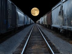 Full moon rising  On two long lines of freights.
