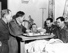 Flying Officer Branz Oliver, 28, center, rests after surviving a crash of a Royal Air Force jet bomber at Offutt Air Force Base on Nov. 3, 1961. According to the story at the time, the aircraft dropped almost immediately after takeoff, bounced off a grassy embankment and skidded across a busy highway without hitting any vehicles. The plane exploded in flames, but all six aboard made it out safely. Here, Oliver is surrounded by four others who were aboard. They are, from left, Chief Technician Peter Benson, Flying Officers William Yates and Richard MacLachlan, and Squadron Leader Clifford Hardman. THE WORLD-HERALD