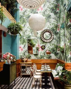 this tropical cocktail and oyster bar in san francisco designed by @kenfulk and @delagrammar is reminiscent of the golden era. a light and fern-filled conservatory is organized beside a sitting area with a cozy bar and vibrant, plant patterned wallpaper.  see more #restaurantinteriors on #designboom @leosoysterbar