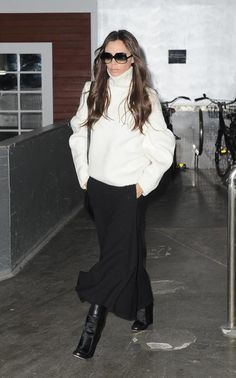 Victoria Beckham in a white cable-knit turtleneck sweater + black midi skirt + black boots