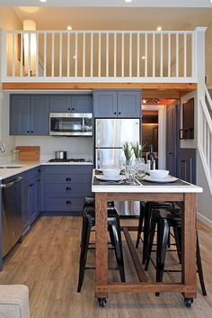 The L-shaped kitchen includes a rolling island/dining table that was custom built for the space, a cooktop, refrigerator, and dishwasher.