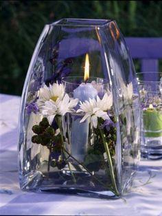 Perfekte Tischdeko für eine lauen Sommerabend: Ein Windlicht mit Schwimmkerzen und dazu Blümchen.