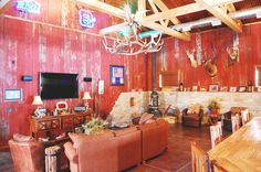 Hunting shack remodel. Tall wooden beam ceiling. Red barn boards for walls. Entertainment area.