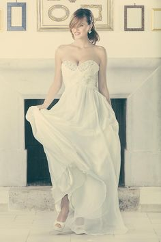 Una leggerissima mussola di seta e un sofisticato motivo a drappeggio rendono questo abito fresco e giovane senza tralasciare la preziosità del ricamo rigorosamente realizzato a mano con gemme perle e cristalli.