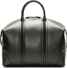 """Structured buffed leather duffle bag in black. Silver-tone hardware. Twin wrapped handles at top. Overlong exposed two-way zip closure at main compartment with tab detail. Tonal piping at bag faces. Embossed logo at bag face. Zippered welt pocket and logo patch at interior. Tonal textile lining. Tonal stitching. Approx. 17.5"""" length x 14"""" height x 8"""" width."""