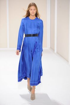 Dress with knife pleats in smalt blue Bandana éperon d'or silk jacquard, belt in indigo blue Evercalf calfskin, mules and ankle bracelets in buckwheat calfskin