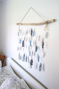 Create your own pretty paper feather wall decor perfect for adding interest to any indoor space. Paper feathers cut with the Cricut Maker and strung on a driftwood branch as coastal boho bedroom decor. Vinyl Crafts, Decor Crafts, Diy Home Decor, Paper Crafts, Feather Wall Decor, Feather Crafts, Craft Storage Containers, Paper Flower Arrangements, Paper Flowers