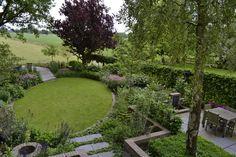 Een landelijke tuin met prachtige planten en uitzicht over de weilanden.