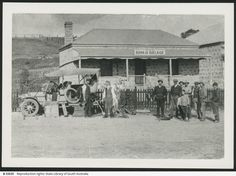 SWAN REACH: The premises of the first Bank of Adelaide in Swan Reach; a group of men and children stand outside watching two other men change a wheel on a parked car which was the first one to come through Swan Reach.
