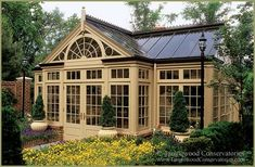 This conservatory is a freestanding pool house with a built-in spa and changing rooms inside. The two-tone color scheme was coordinated with the wood trim and the brick and mortar of the main house. #conservatorygreenhouse