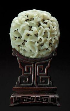 Chinese stone carving Belle et rare plaque en jade blanc ajouré représentant un phénix perché sur une branche d'arbre dont les fleurs et les feuillages sont traités en enroulement, la bordure en forme de lotus. Au revers l'encadrement sculpté de huit chimères opposées. Période Qianlong (1736-1795) L: 9cm. Posé sur un socle en bois ajouré postérieur