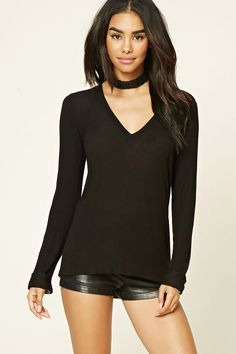 A semi-sheer, knit top featuring a V-neckline, long cuffed sleeves, and a form-fitting silhouette.