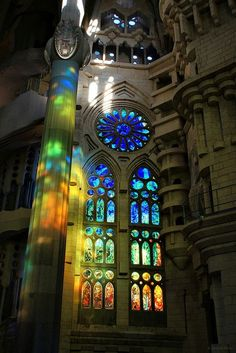 Beautiful art work of stained glass in a church (showing the sun filtering through, casting colors).