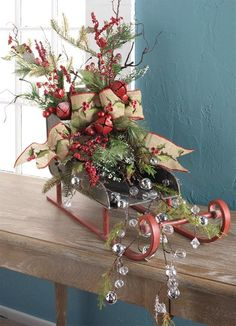 Collection of Christmas decorations from RAZ using sleighs and sleds.