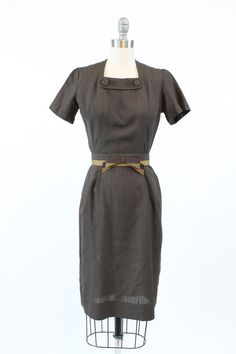 Sweet 1950s wiggle dress! Made in a chocolate brown cotton. Fitted wiggle style, center back metal zip. The collar has charming button detail.