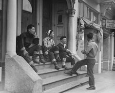 High school boys of Japanese ancestry on a busy Saturday afternoon, watching preparations for the evacuation due in a few days. San Francisco, 1942.