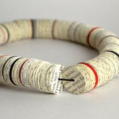 "This necklace consists of many small disks, cut from book pages and different papers in red, gray and black.The disks have a diameter of 2.2 cm (0.87 ""). The length of the necklace is about 50cm (20""). It is sprayed with protective lacquer and splash proof. Paper necklace from book pages with red gray by PaperStatement, €65.00"