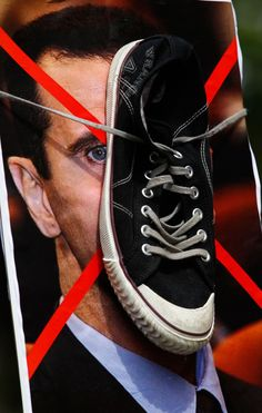 A poster of Syria's President Bashar al-Assad with a shoe attached is held up during a demonstration outside the Syrian embassy in London. Source: Reuters
