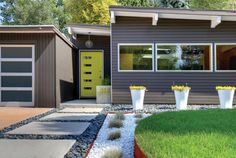 Mid-century updated facade with yellow front door, brown walls and white planters. From Best Construction.