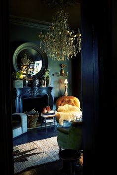 A buttercup yellow tufted chair becomes the focalpoint in this dark teal room with its antique black fireplace. Notice how the yellow compliments the golden chandelier. For the brave of heart!
