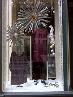 Look closely and you will see that the hanging props in this store window are made from rolled up newspaper and joined with ornaments in the center to create decorative bursts.  *Could put a diaper in the center*
