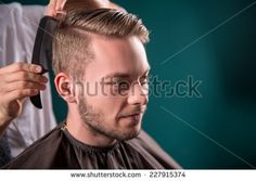 hairdresser  does   hair  with black comb of handsome satisfied  client in  professional  hairdressing salon  - stock photo