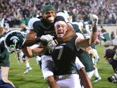 GO GREEN!    B.J. Cunningham (3) and Keith Nichol (7) of the Michigan State Spartans celebrate Nichol catching a game-winning 44 yard touchdown pass from Kirk Cousins as time ran out to defeat the Wisconsin Badgers 37-31 at Spartan Stadium on October 22, 2011