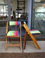 Folding chair with back and seat upholstered in bright coloured fabric.