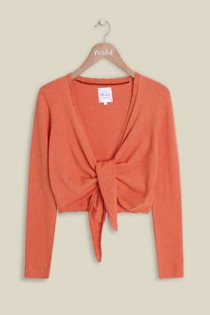 Our Tina Tie Front Cardi took inspiration from the free spirit of a true bohemian lifestyle. The bright coral cardi will brighten and glam any outfit, while offering an elegant fit through the tie, finishing with delicate trim detailing. Also available in Holiday.
