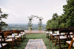 Hilltop Tennessee wedding ceremony with vintage rugs and a flower arch