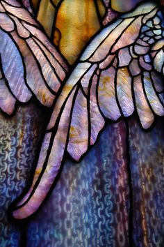 Tiffany Glass Wings. Note the patterns in the glass pieces. They were created to give a sense of depth and texture and then used almost as paint to create the image. See the striations on the feathers? The chain mail of the skirt? The play of swirls in the bodice looks like light reflecting off of gold or bronze. Amazing.