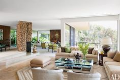 The den includes sofas and a cocktail table custom made by Dunning; the James Mont ottoman is covered in a Jim Thompson silk, and the bespoke rug is by Edward Fields | archdigest.com