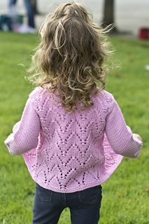 Openwork arches are featured prominently on the body of this dainty baby's cardigan. The sleeves are Stockinette stitch, with the arch motif repeated once immediately above the cuff. An extended button tab is used for closure at the yoke. Sleeves are indented for ease in dressing and all edges are finished in garter stitch.