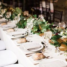 Going for a full on fall vibe,  these #BridesRealWedding tables featured garlands of magnolia leaves studded with white roses and burgundy dahlias | Tap link in bio for more fall wedding inspo! : @laurenfair : @floresta_nyc