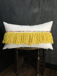 Inspired by everything Moroccan, this pillow features beautiful details. A row of yellow fringe with colourful wooden beads handsewn above. The front and back of the pillow is a natural cotton twill. Zipper closure.  Fits a 12 x 20 or slightly larger insert (insert not included)  Actual pillowcase measures approximately 19 X 11  FREE SHIPPING TO U.S. & CANADA with tracking number