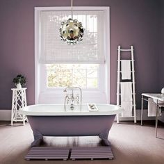 Paint the outside of a freestanding roll-top bath the same colour as your walls for a coherent look. This deep plum shade is perfect for creating a warm, inviting feel, and it contrasts beautifully with glossy white woodwork, sanitaryware and furniture