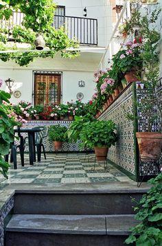 Me recuerda a la antigua casa del pueblo, mismo modelo de azulejo distinto color, pero lleno de macetas..