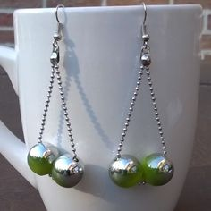 oorbellen met  2 groen-zilverkleurige kunststof kralen op bolletjesketting €4,00