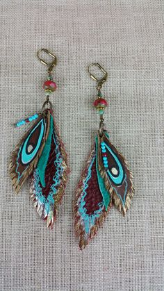 One of our smaller pairs of feather earrings, these little beauties are full of impact! Bold and royal colors make these so very special. Brown and red leather feathers are painted with turquoise, bro
