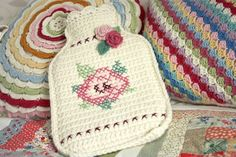 A cutie crochet and cross stitch hot water bottle with roses.