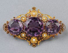 Antique 14kt Gold and Amethyst Brooch, set with three circular-cut amethysts within a scrolling floral and foliate mount, seed pearl accents, lg. 2 1/8 in. Victorian or Victorian style.