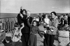 """1952. Charlie Chaplin avec son épouse Oona et leurs quatre enfants sur le pont du paquebot """"Queen Elizabeth"""" en rade de Cherbourg avant la dernière étape de leur voyage depuis les États-Unis vers Southampton .Chaplin viens d'apprendre qu'une enquête a été ordonné sur ses activités aux USA qualifié d'anti-Americain . Photo : Daniel Filipacchi /Paris-Match."""