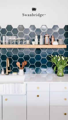 A quartz countertop that makes a great marble alternative: Cambria Swanbridge. This white countertop is marbled with subtle grays and pin points of dark charcoal. With gentle movement this kitchen countertop can be used in modern farmhouse spaces or transitional kitchens. Swanbridge pairs well with this hexagon tile backsplash and open shelving. #MyCambria